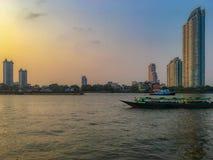 小船在有美丽的清楚的日落天空和居民住房的河 库存照片