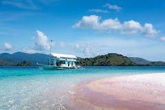 小船在桃红色海滩的清楚的水中在科莫多国家公园, Indon 库存照片