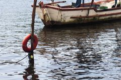 小船在水中停泊了在与红色浮体的海岸和反射 免版税库存照片