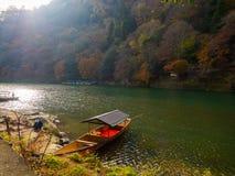 小船在秋天风景的、黄色、橙色和红色秋天树和叶子,五颜六色的叶子一个湖在秋天公园 库存图片