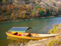 小船在秋天风景的、黄色、橙色和红色秋天树和叶子,五颜六色的叶子一个湖在秋天公园 免版税库存照片
