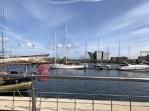 小船在贝尔法斯特怀有,在距离的力大无比的大厦 库存照片