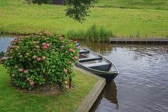 小船在运河停放了在美丽的八仙花属灌木附近 库存图片