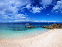 小船在透明的海洋漂浮在白色沙滩旁边 免版税库存照片