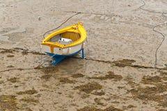 小船在Erquy港口在沙子的在与多云天空的衰退浪潮 免版税库存图片