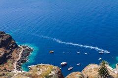 小船在Oia村庄附近海岸的海圣托里尼的 库存图片