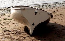 小船坐在海滩的沙子 库存图片