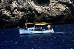 小船岩石海岸的捕鱼 免版税库存照片