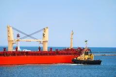 小船帮助回旋船用力拖 库存图片