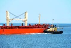 小船帮助回旋船用力拖 免版税库存图片
