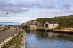 小船库和滑动式造船架在Ballintoy在北爱尔兰北部安特里姆海岸怀有有它的石被修造的船库的o 图库摄影