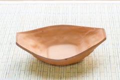 小船形状烘烤在竹席子的黏土器物 库存照片