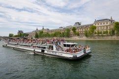 小船拥挤了与观光沿塞纳河的游人在巴黎 免版税库存图片