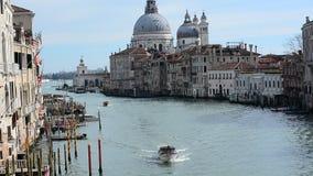 小船早晨交通在大运河的在威尼斯,在Accademia区,有圣玛丽亚德拉Salu大教堂的  股票录像