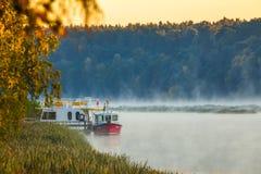 小船早晨有雾的风景在Nemunas河 免版税库存图片