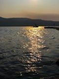 小船横穿在海洋的日落反射 免版税库存照片