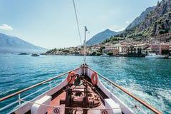 小船游览:小船弓、看法在天蓝色的大海,村庄和山脉 拉戈di加尔达,意大利 免版税库存图片