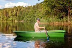 小船烘干了老早晨伸出结构树水的早期的渔夫 库存图片