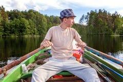 小船烘干了老早晨伸出结构树水的早期的渔夫 免版税库存图片