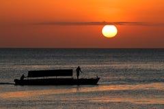 小船现出轮廓反对日落 库存图片