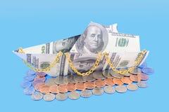 小船由金钱制成在蓝色背景 免版税库存照片