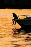 小船男孩摇晃的英尺他的在船首 免版税库存照片