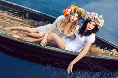 小船的两个美丽的女孩 免版税图库摄影