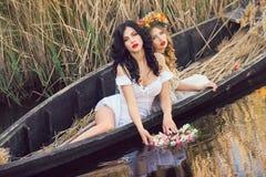 小船的两个美丽的女孩 库存图片