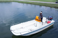 小船的人在高尔夫球场湖 免版税库存照片