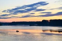 小船的剪影有渔夫的河的在黎明 背景,大量文本的空间 免版税库存照片