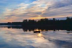 小船的剪影有渔夫的河的在黎明 免版税库存图片