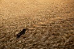 小船的剪影背景通过Th的一条河跑 图库摄影