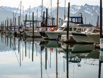 小船的反射有山的在背景在Seward 图库摄影