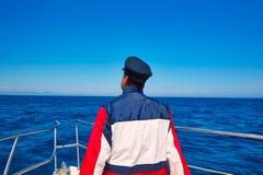小船的后方海员帽人航行海海洋 免版税库存图片