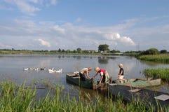 小船的孩子在湖 免版税库存照片