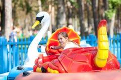 小船的孩子-天鹅在公园乘坐 免版税库存图片