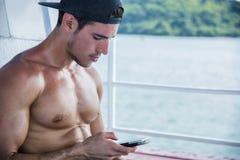 小船的年轻人使用手机,赤裸上身 免版税库存照片