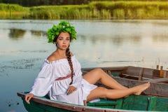 小船的年轻性感的妇女在日落 女孩有在她的头的一个花花圈,放松和航行在河 幻想艺术 免版税库存照片
