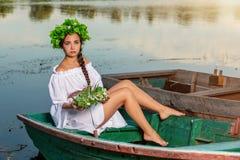 小船的年轻性感的妇女在日落 女孩有在她的头的一个花花圈,放松和航行在河 幻想艺术 库存照片