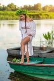 小船的年轻性感的妇女在日落 女孩有在她的头的一个花花圈,放松和航行在河 幻想艺术 库存图片