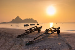 小船的拖车在与金黄日落的海滩 免版税库存图片
