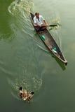 小船的未认出的鸭子农夫在死水引导他的鸭子 免版税图库摄影