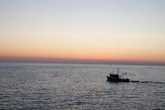小船的渔夫在严重的日落 库存图片