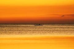 小船的渔夫在日落期间 库存图片