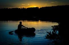 小船的渔夫在日落 库存照片
