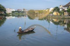 小船的渔夫在网络向星期四好的妙语河,会安市,越南 免版税图库摄影