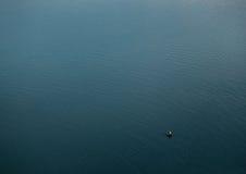 小船的渔夫在蓝色大湖 库存照片
