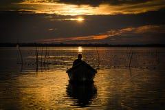 小船的渔夫在黎明 免版税库存照片
