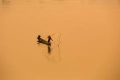 小船的渔夫是传染性的鱼在泰国的湄公河- L 免版税库存图片