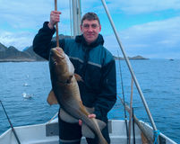小船的渔夫用鳕 免版税库存图片